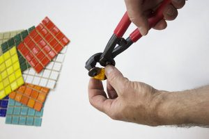 Cutting Vitreous Glass Mosaic Tile diagonally to make triangles.