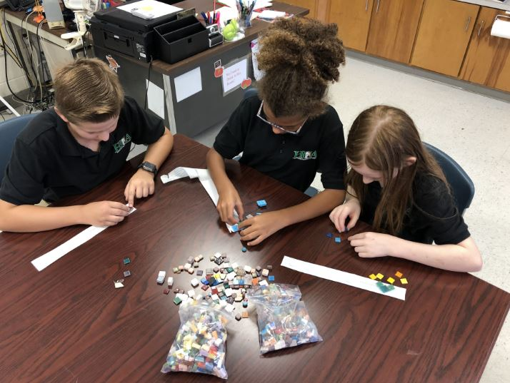 These students are using materials from the mosaic salvage assortment to create their designs.