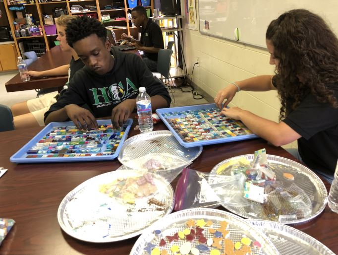 Students create the mosaic lines on paper strips, which are then transferred to the cross.
