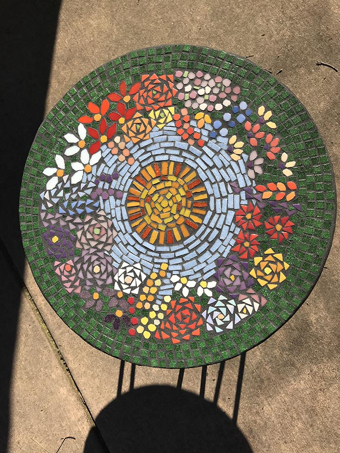 Julie Landberg's finished mosaic table with sun in sky design over field of flowers.